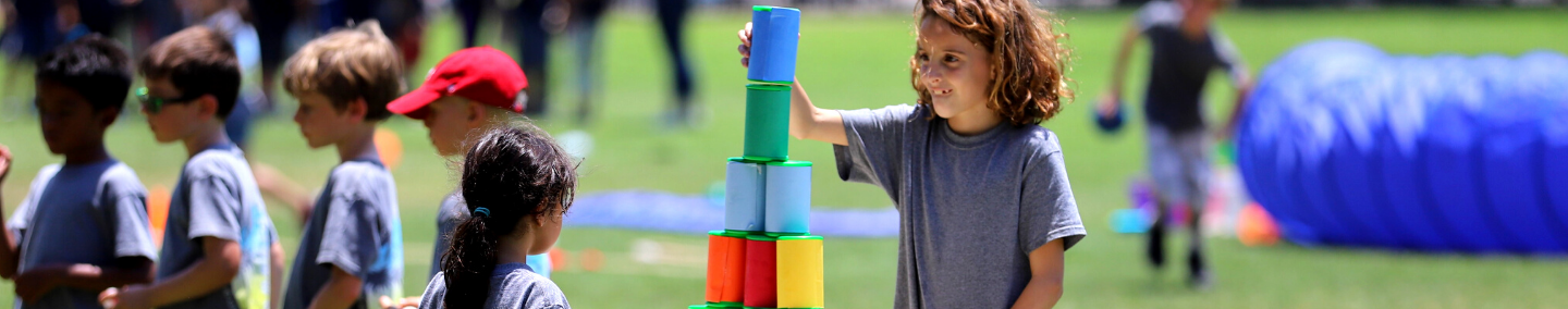 A young boy is playing a stacking game at Summer Daze Camp.